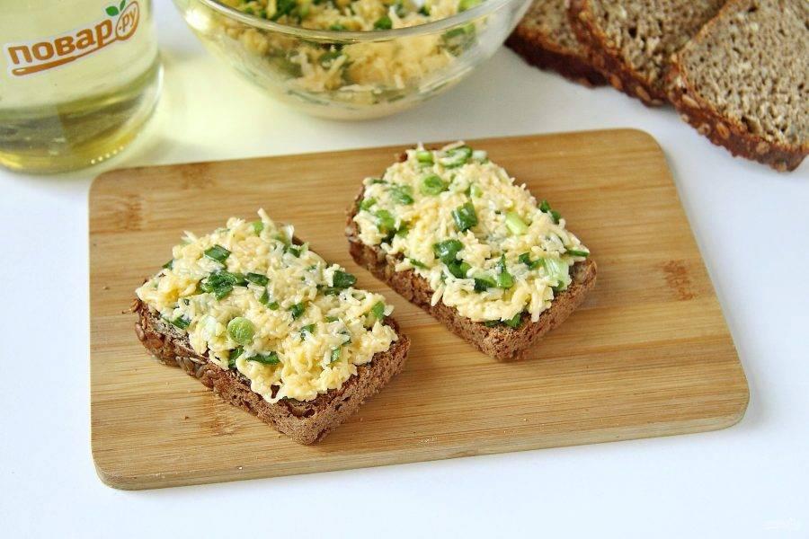 Хлеб или батон нарежьте тонкими ломтиками и намажьте сырной массой.