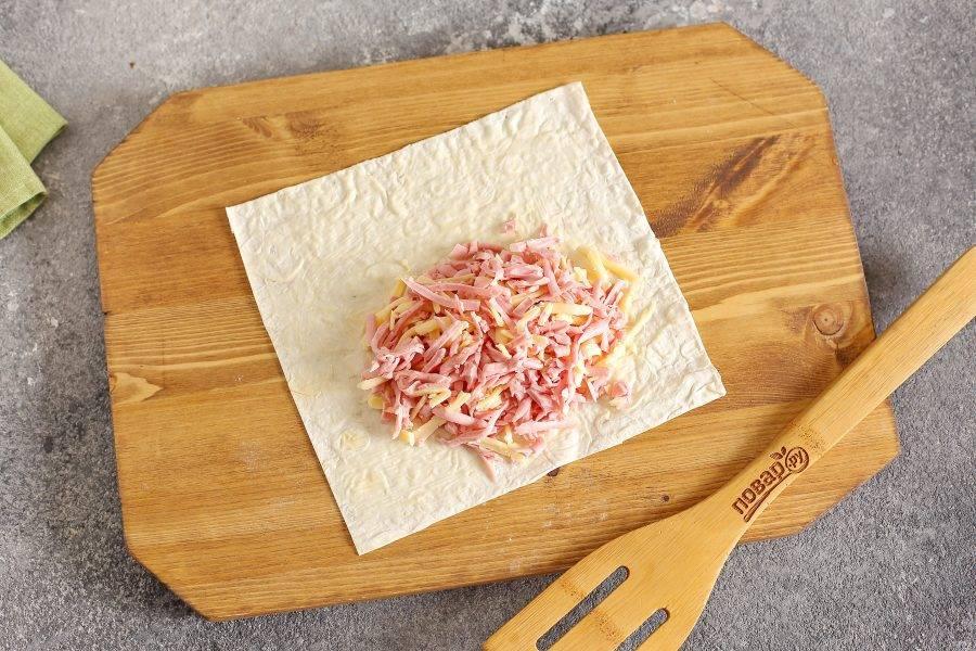 Лаваш нарежьте на квадраты. У меня из каждого лаваша выходит 4 штуки. Смажьте лаваш размягченным сливочным маслом и ближе к одному краю распределите начинку.