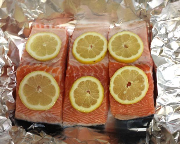 Уложить порционные куски на фольгу. На лосося положить кружочки лимона. По желанию добавьте специй.