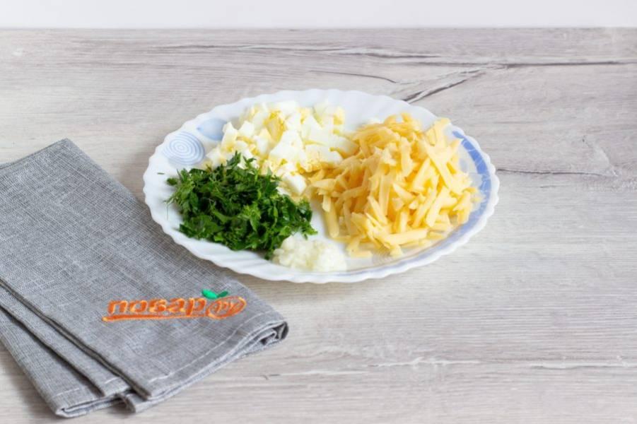 Тем временем сыр натрите на крупной терке, яйцо мелко нарежьте, чеснок и зелень порубите.