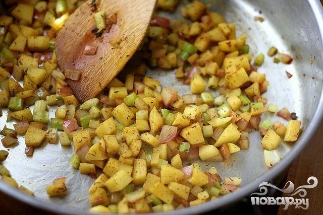 3. Между тем нагреть оливковое масло в сковороде. Нарезать сельдерей, лук и яблоко. Добавить  сельдерей, лук, яблоко, тмин, карри и корицу в сковороду. Жарить, пока не яблоко и овощи не смягчатся. Снять сковороду с огня и отставить в сторону.