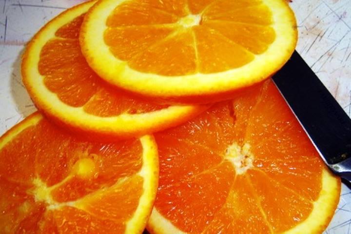 Апельсины и лук нарежьте колечками и выложите поверх мяса в мультиварке. Включите режим выпечки и готовьте 1 час. На стол подавайте, посыпав свежей зеленью.