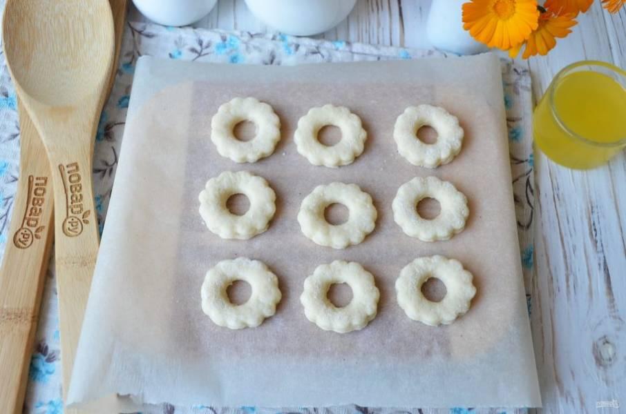 Раскатайте тесто толщиной не более 1 см. Вырубкой для печенья большой выдавите кружочки. Меньшей вырубкой сделайте дырочки. Отправьте печенье на пергамент и в духовку на 12-15 минут.