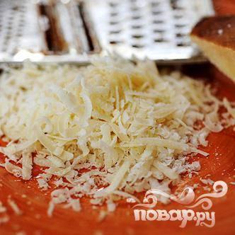 С помощью терки измельчить сыр пармезан.