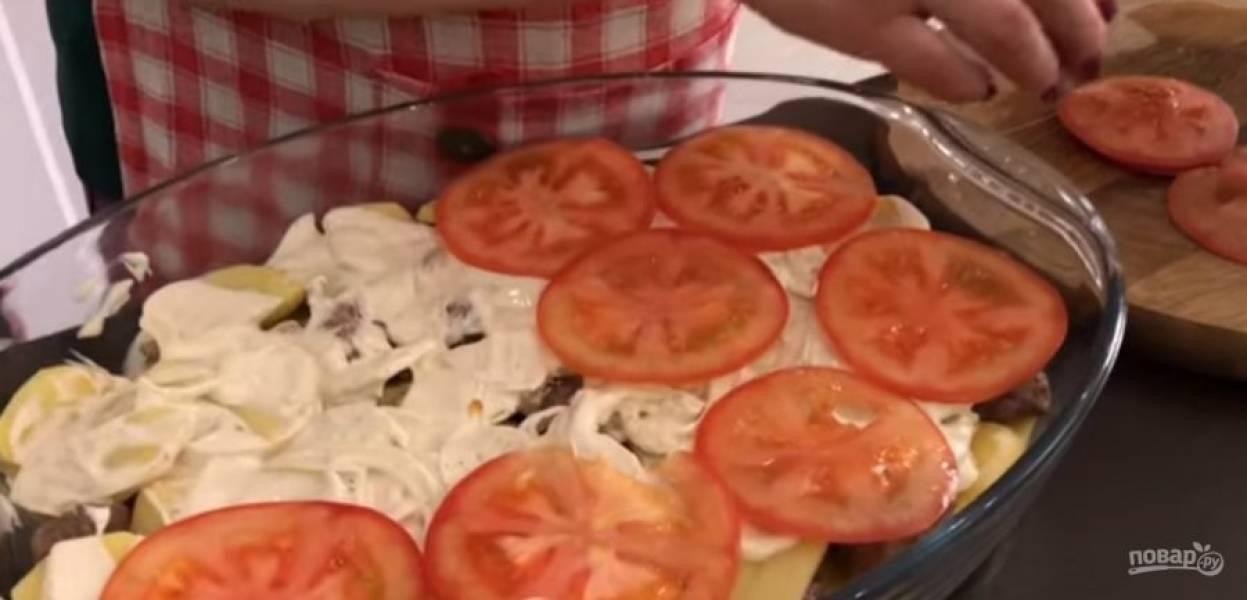 4. Сверху выложите нарезанные помидоры, посолите и поперчите их. Посыпьте все сыром и накройте фольгой. Выпекайте в разогретой до 170 градусов духовке на 40 минут до готовности мяса.