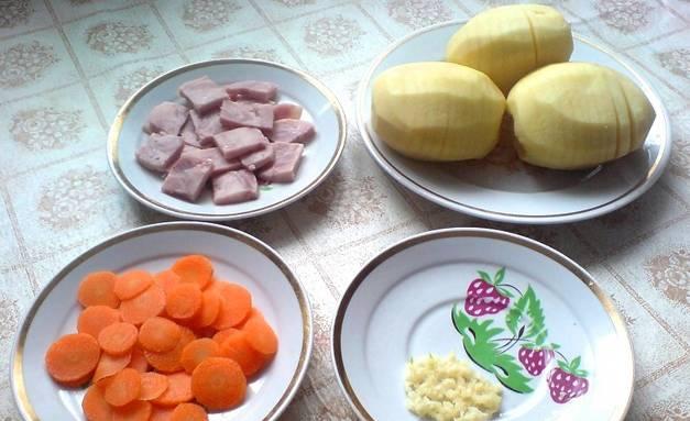 Промываем и очищаем овощи. Морковь нарезаем тонкими кружочками, а ветчину режем кубиками. Чеснок пропускаем через пресс. На очищенном картофеле делаем глубокие надрезы (не до конца), не забываем посолить.