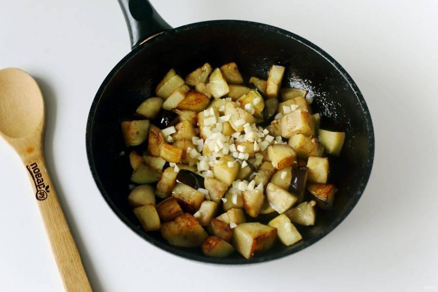 Баклажаны посолите и обжарьте на среднем огне периодически помешивая до полной готовности. Затем добавьте измельченный чеснок и готовьте все вместе еще около 2-3 минут.