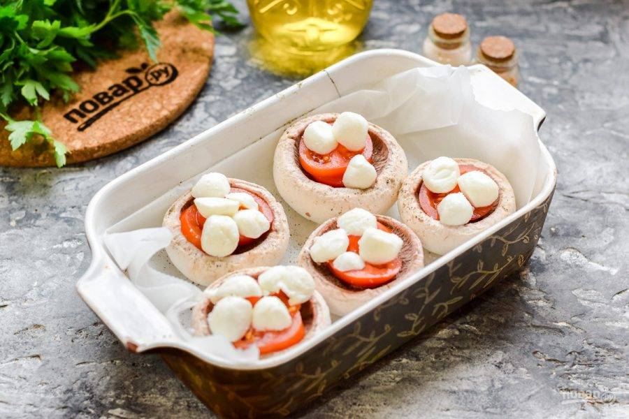 Шарики моцареллы разрежьте пополам и выложите поверх помидоров.