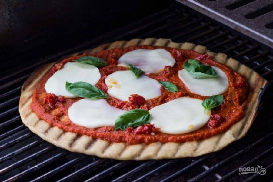 6.Смажьте обильно приготовленным томатным соусом, выложите ломтики сыра и добавьте несколько листочков базилика. Отправьте в духовку или на гриль еще на 5-7 минут.