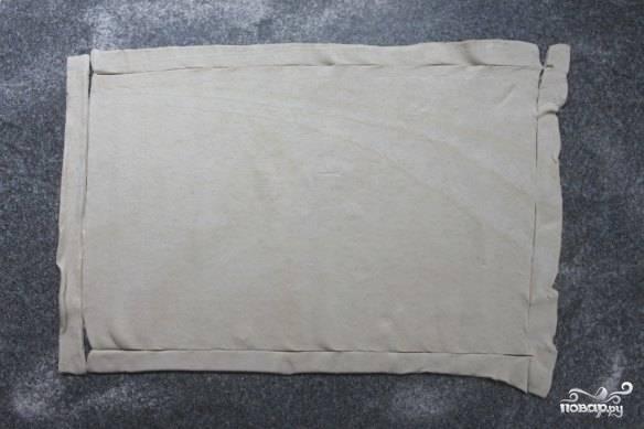 Тесто раскатайте по размеру противня и аккуратно отрежьте по полоске в 1 см с каждой стороны.  Сформируйте из полученных полосок своеобразные стенки по краям теста.