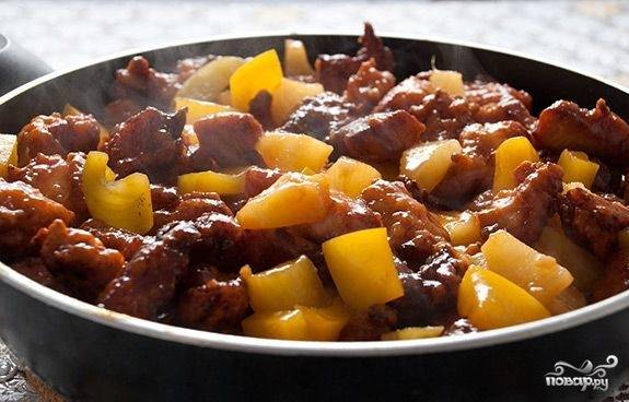 Добавляем обжаренные куриные кусочки в сковороду с соусом и всё перемешиваем. После этого накрываем крышкой и тушим на маленьком огне еще 2-3 минуты. Блюдо готово к подаче на стол. Красиво выкладываем его на тарелку и удивляем гостей.