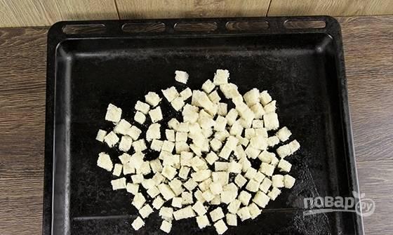 Батон нарежьте кубиками, удалив корки. Выложите их на противень. Сбрызните батон маслом, убрав чеснок.