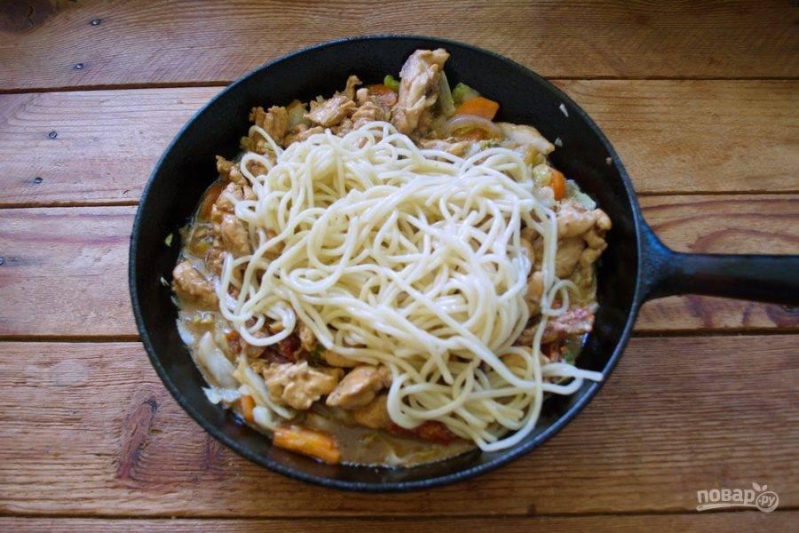 В сковороду к овощам переложите обжаренное мясо. Добавьте отваренные спагетти. Перемешайте.