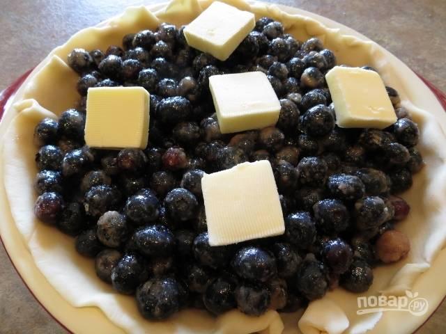 4.Сливочное масло разделите на кусочки и выложите поверх ягод.