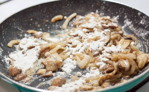 5. Когда грибочки выпустят жидкость, всыпать на сковороду муку.