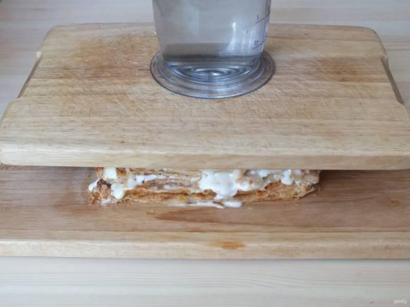 Прикройте верхний слой торта пищевой пленкой и поставьте гнет. Оставьте в таком виде на 30-60 минут.