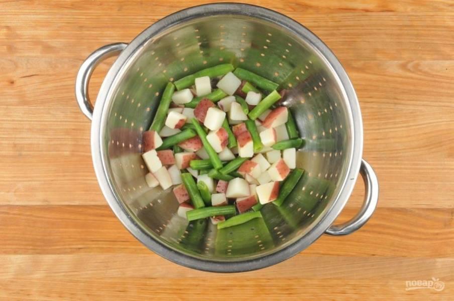 2. Затем доведите до кипения 2 кружки подсоленной воды вместе с картофелем. Варите его в течение 7 минут. Потом добавьте фасоль и варите ещё 4 минуты. После этого слейте воду.