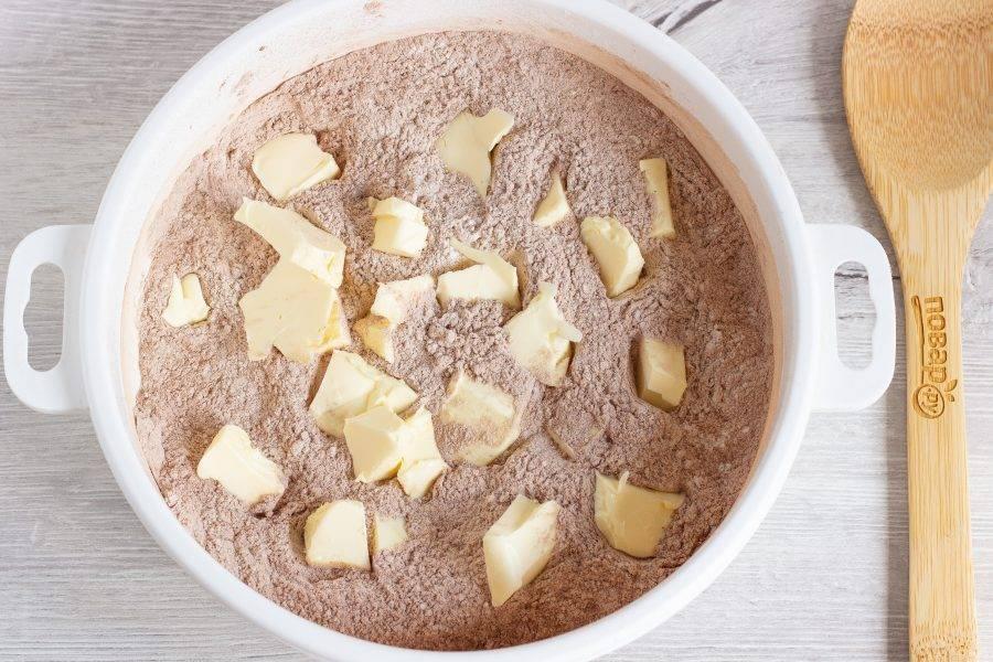 Затем добавьте кусочки холодного сливочного масла и разотрите смесь руками до появления комочков.