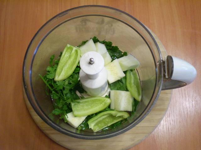 Складываем зелень, перец и кабачок в комбайн. Добавляем воду. Включаем прибор, и все тщательно измельчаем.