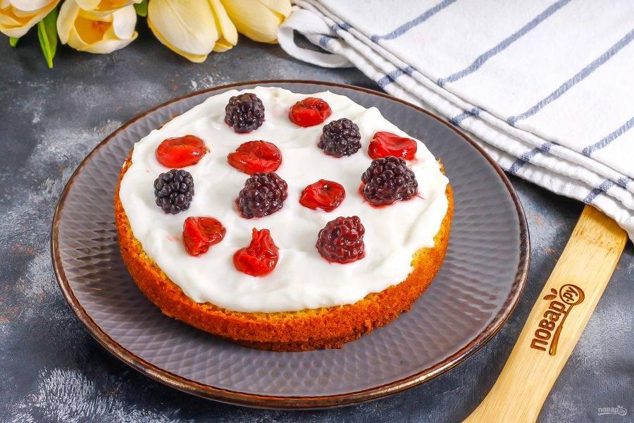 Разрежьте бисквит на три части, на первый корж выложите треть сметанного крема и ягоды. Если используете вишню, очистите ее от косточек.