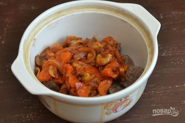 Добавьте в пассерованные овощи томатную пасту, обжаривайте их еще несколько минут. Выложите обжаренное мясо и овощи в горшочек.