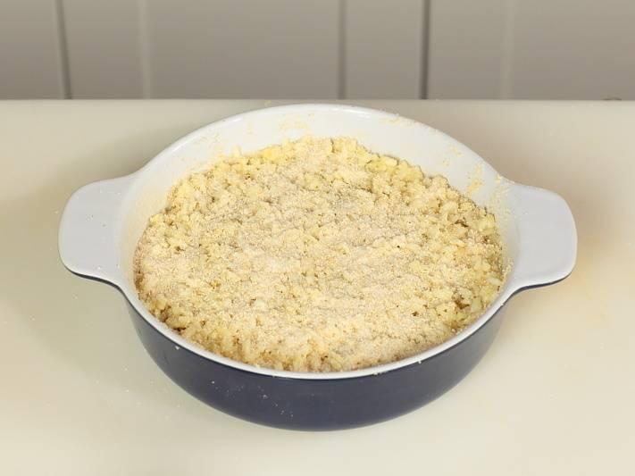 Фарш накройте рисом и посыпьте сухарями. Выпекайте 30 минут при 180 градусах.