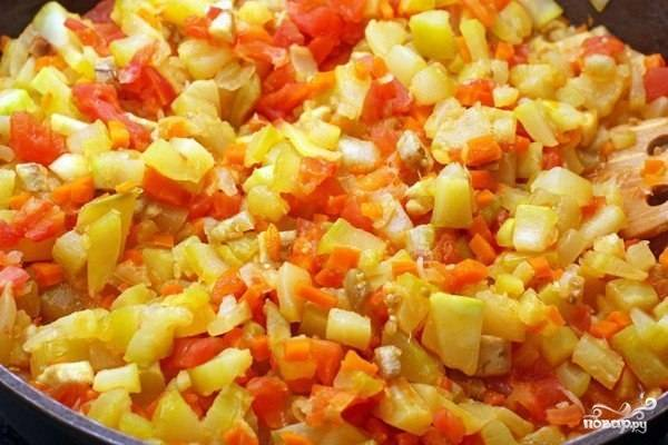 Вымойте морковь, томаты, кабачки и зелень. Очистите от шкурки морковь, лук и кабачки, также очистите их от семян. Порежьте небольшими кубиками кабачки, морковь и томаты. Зелень мелко нашинкуйте. Налейте на сковороду масло и обжаривайте лук, пока тот не станет золотым. Затем добавьте морковь, жарьте еще минут 7. После выложите в сковороду кабачки, жарьте еще 10 минут. Добавьте томаты и готовьте примерно 5-7 минут, постоянно помешивая.