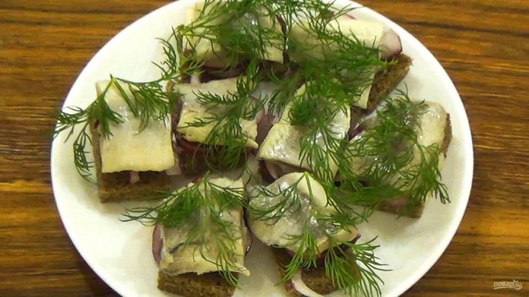 3.  На ломтик хлеба выложите замаринованный лук, кусочек сельди и укроп. Приятного аппетита!