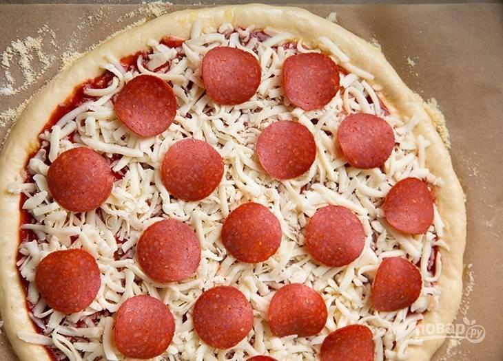 На соус потрите сыр и распределите его, оставляя ободок. Поверх сыра выложите тонко нарезанные кружочки пепперони. Края пиццы смажьте растительным маслом.
