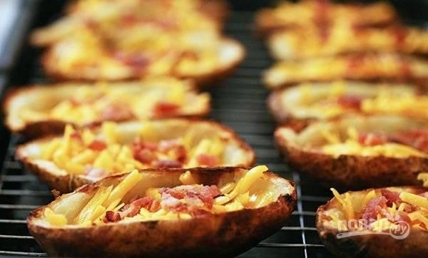 4.Обжарьте бекон на сухой разогретой сковороде в течение 10 минут, затем переложите на салфетку и после остывания нарежьте мелко. Выложите кожуру на противень и посыпьте солью, перцем, выложите немного бекона и тертый сыр. Готовьте около 2 минут.