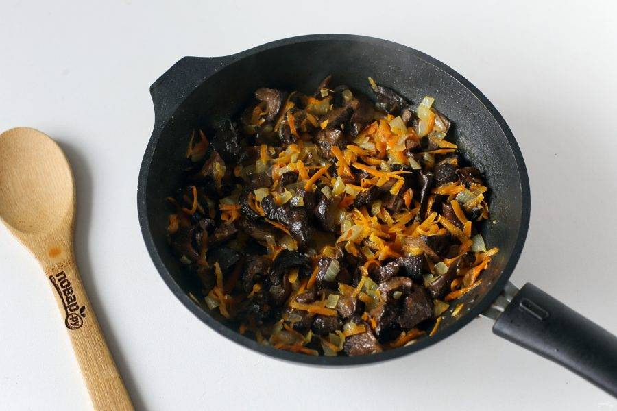 Добавьте отваренные заранее грибы и обжарьте все вместе в течение 5-7 минут.
