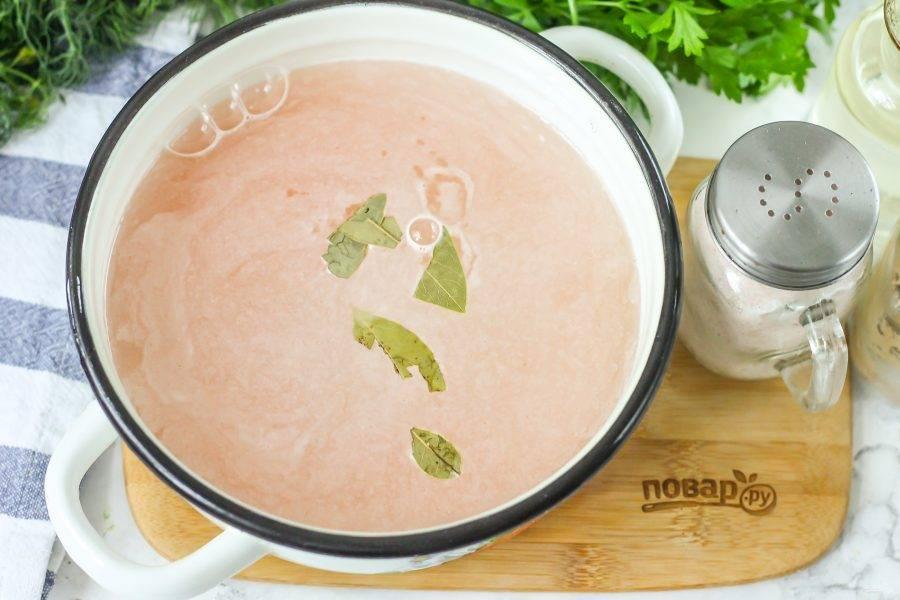 Высыпьте чечевицу в кастрюлю, влейте горячую воду и добавьте лавровые листья. Поместите емкость на плиту и доведите до кипения ее содержимое. Удалите образовавшуюся пену и отварите чечевицу примерно 20 минут.