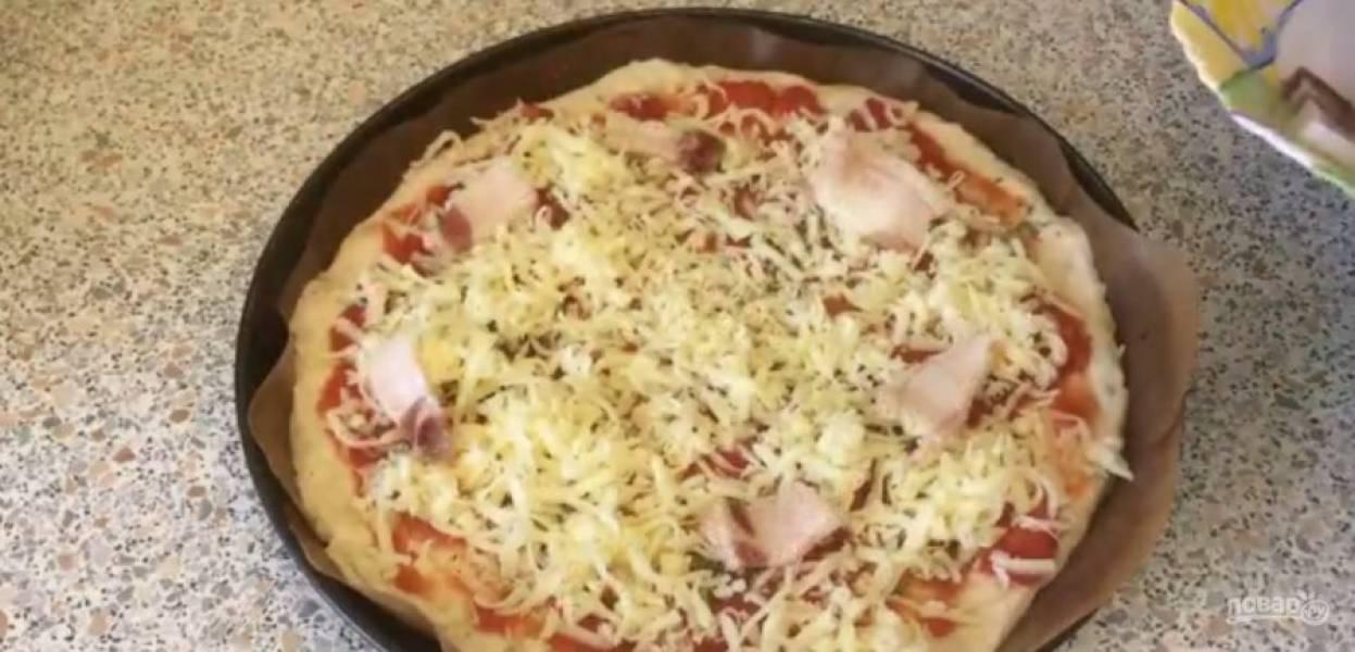5. Оставьте тесто для отдыха на 15-20 минут. Распластайте тесто в толстый пласт размером с будущую пиццу. Распределите по нему консервированные измельченные томаты, специи, черный перец и тертый сыр.