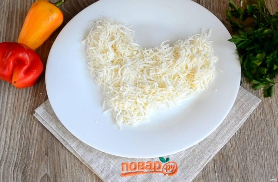 Первым слоем на дно плоской тарелки выложите плавленый сыр, придайте ему форму петушка.