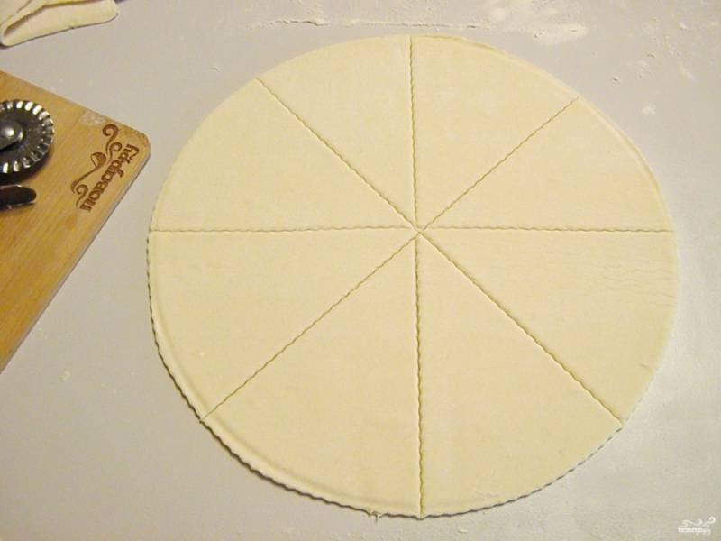 Размороженное тесто просто разверните, раскатывать его не нужно. Вырежьте круг. Круг разделите на 8 частей.