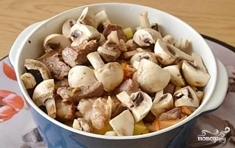 Спустя минут 7 выключите плиту. Соберите блюдо. В кастрюлю на дно уложите картофель, дальше — ингредиенты со сковороды, а в конце — грибы. Всё посолите и поперчите.