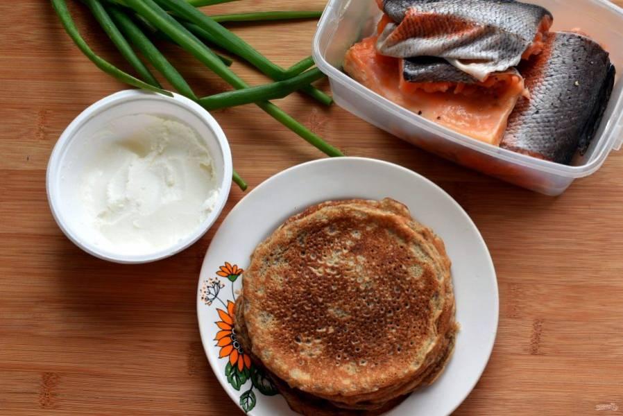 Пеките блинчики как обычно, лучше на сковороде небольшого диаметра – так они будут более симпатичными. Готовые блинчики выкладывайте на тарелку и сохраняйте теплыми. Для начинки приготовьте творожный сыр комнатной температуры. Зеленый лук нашинкуйте, малосольную форель разберите на тонкие кусочки. Особенно вкусна форель домашней засолки.