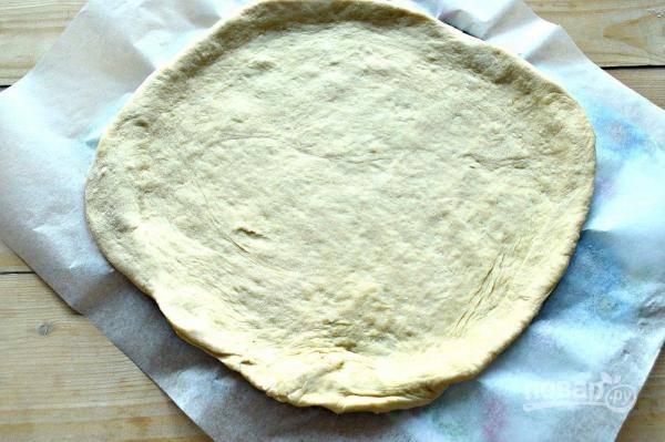 9. Когда тесто хорошо подошло, разделите его пополам. Раскатайте одну часть, выложите на лист пергамента.