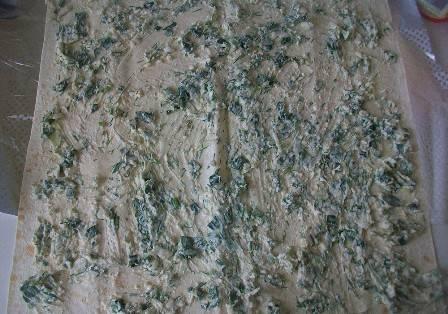 Раскладываем лаваш, равномерно намазываем его начинкой из сыра и зелени.