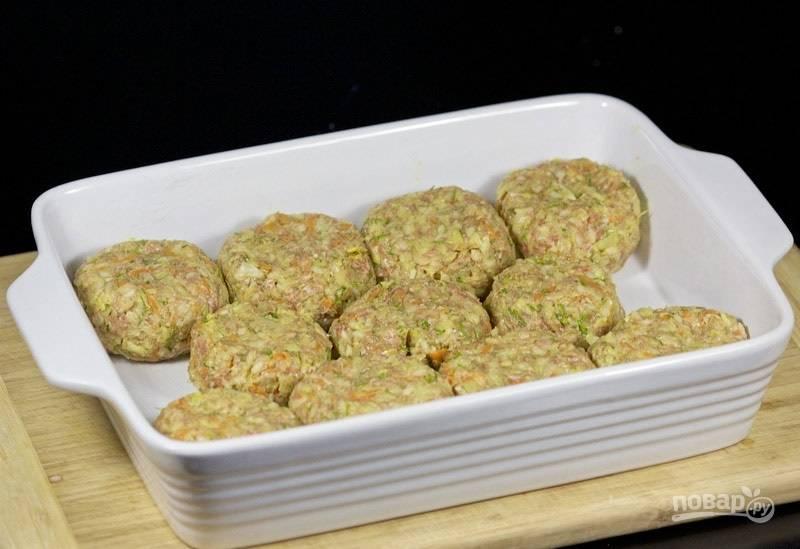 13.Из фарша сформируйте небольшие котлеты или тефтели, выложите их в форму для запекания и залейте соусом.