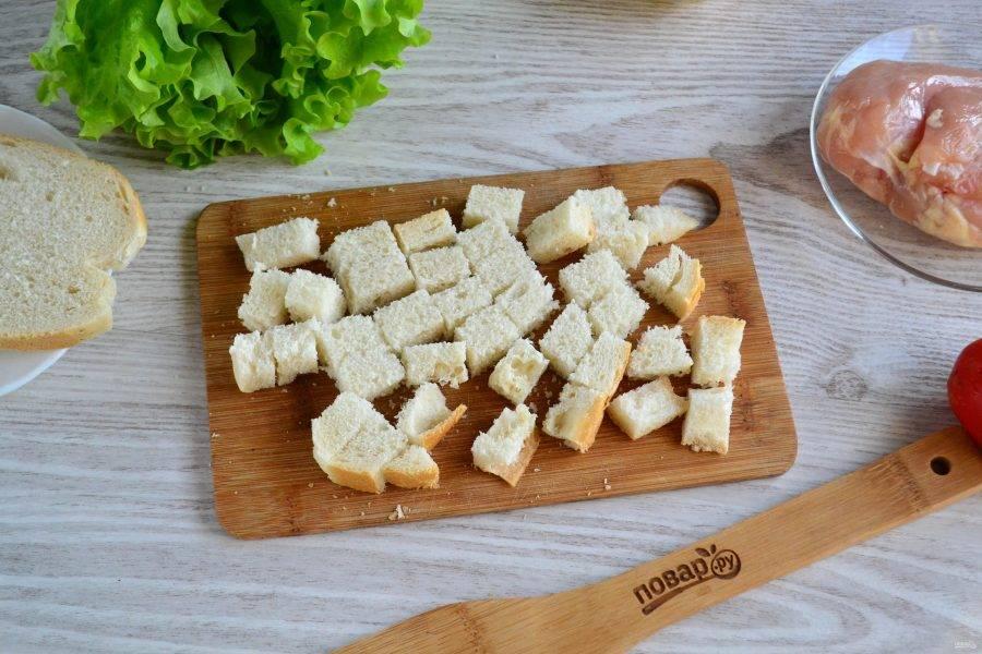 Первым делом приготовьте домашние гренки. Несколько ломтиков хлеба нарежьте небольшими кубиками.