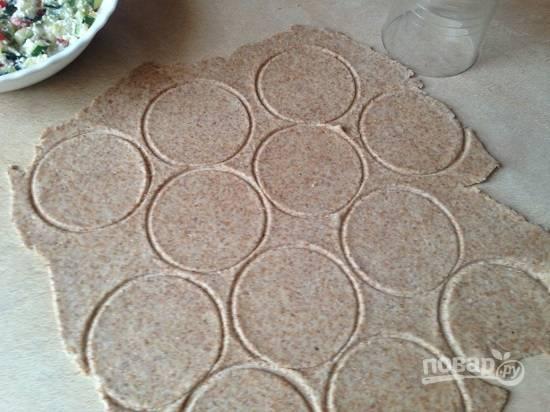 Раскатываем тесто в очень тонкий пласт и стаканом вырезаем кружочки.