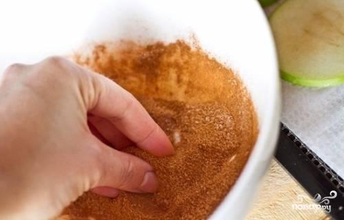 Разогрейте духовку до 70 градусов. Застелите противень пергаментной бумагой, на которую затем уложите яблоки. А в миске смешайте корицу с пудрой.