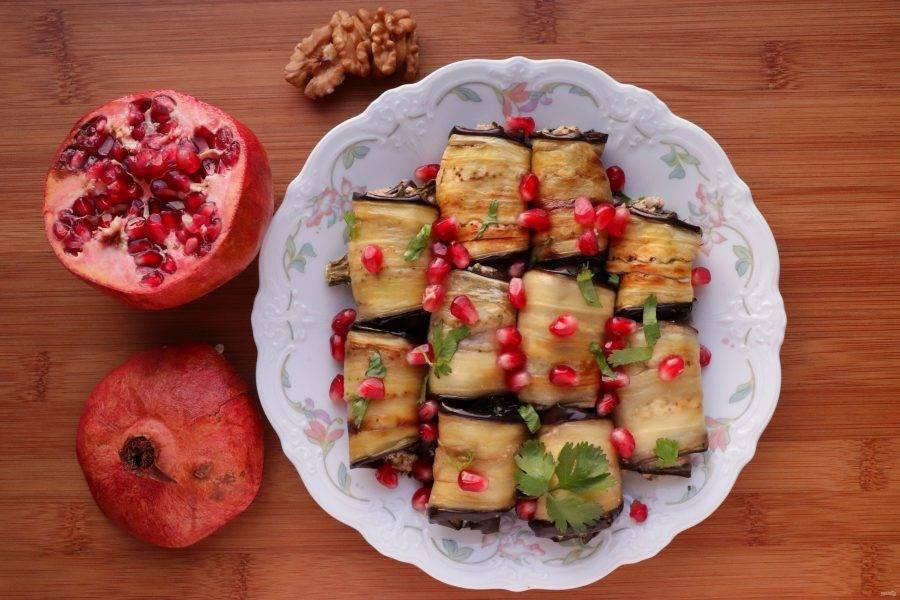 Выложите рулетики из баклажан на тарелку, присыпьте зернами граната, листьями кинзы и измельченными орехами. Баклажаны в ореховом соусе готовы. Приятного аппетита!