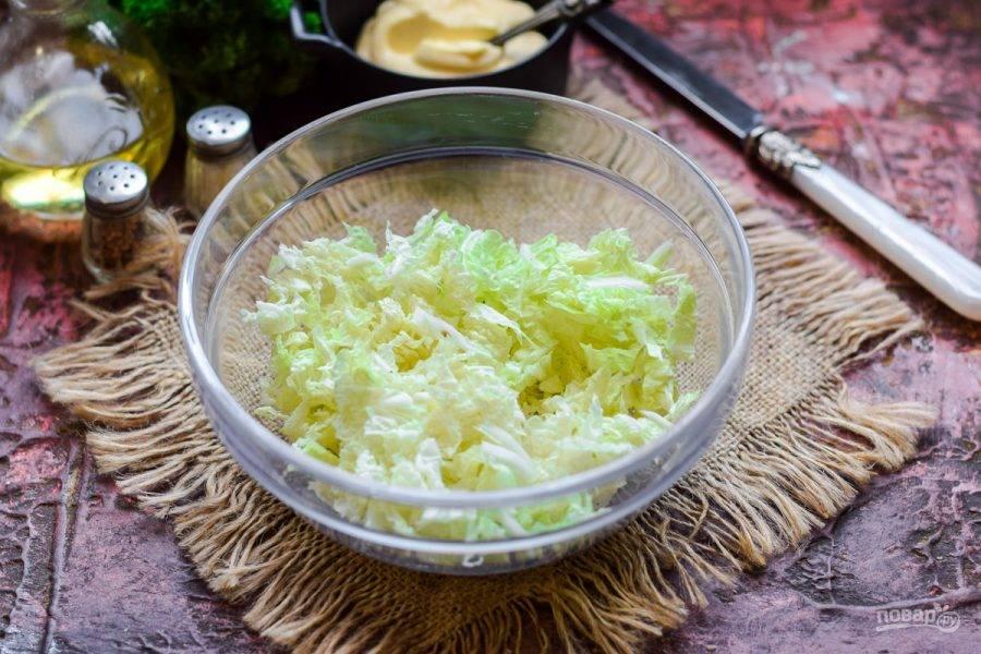 Пекинскую капусту нарежьте тонкими полосками, переложите в салатник.