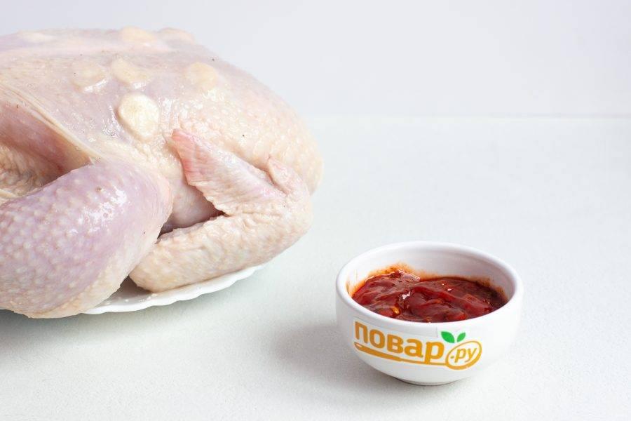 Для маринада смешайте кетчуп и аджику. Кусочками чеснока нашпигуйте курицу на грудке под кожей. Натрите всю курицу солью.