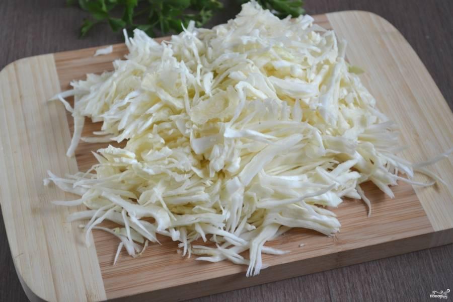 Тем временем нашинкуйте капусту, как на борщ, а затем хорошо помните руками.