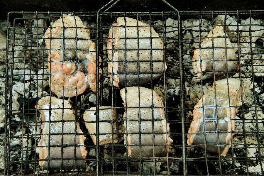 Затем выложите рыбу на решетку и сразу отправьте на мангал с раскаленными углями.