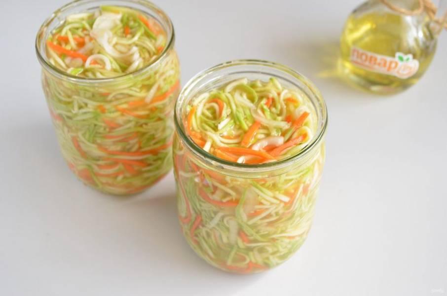 6.  Разложите салат по баночкам, накройте крышками и стерилизуйте 20 минут. Время засекайте с момента закипания воды в кастрюле, она должна доходить до плечиков банок.