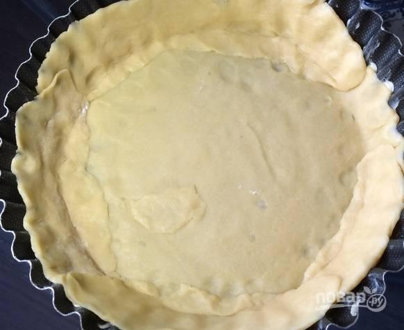 Форму для выпечки смазываем маслом. Тесто делим пополам. Из одной половины выкладываем основу тарта, а из другой формируем бортики.